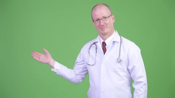 Thumbnail for Happy Mature Bald Man Doctor Showing Something Against Green Background
