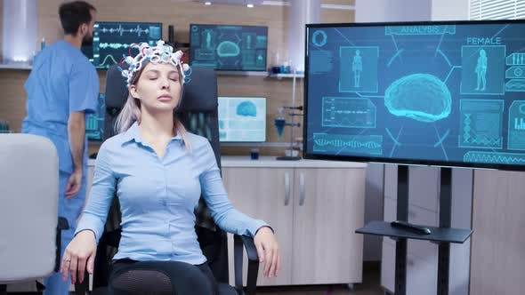 Thumbnail for Young Female Patines Sitting on a Chiar and Wearing Brainwaves Scanning Headset