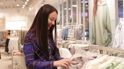 Pretty Young Woman Choosing Clothes in a Clothing Store