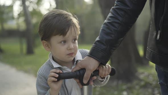 Fröhlicher kaukasischer kleiner Junge reitet Roller im Sonnenlicht mit junger männlicher Hand, der Lenkrad zieht