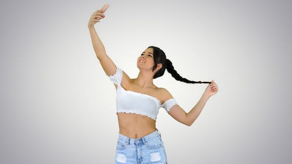 Thumbnail for Cute brunette girl takes a selfie and dancing on gradient