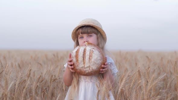 Thumbnail for Bread Grower Kid Girl, Small Fair Haired Farmer Daughter Bites Tasty Baked Bread and Smiles Standing