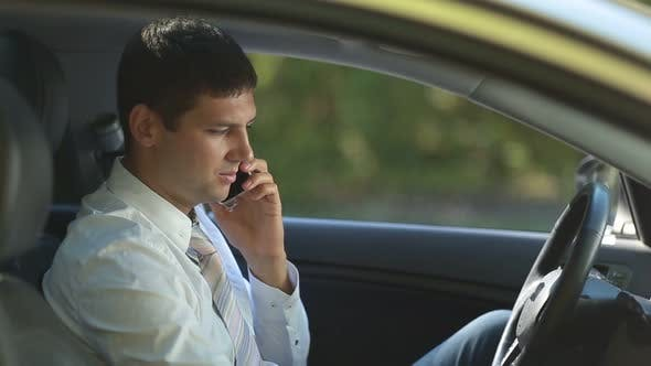 Cover Image for Busy Business Executive Talking on Phone in Car
