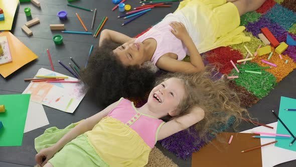 Cover Image for Little Multiracial Girls Lying on The Floor, Laughing and Enjoying Holidays