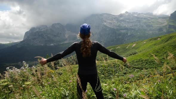 Thumbnail for Man Hiker with Long Hair Raises Hands Up in Mountains Enjoying Beautiful View