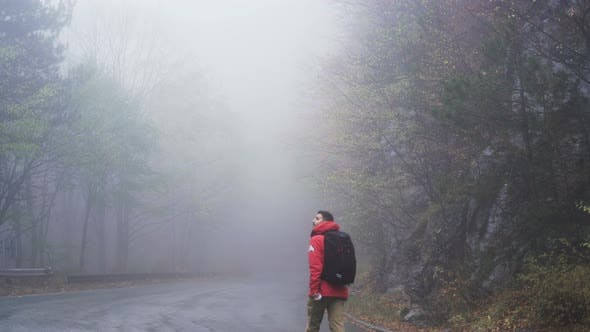 Thumbnail for Man Walking on a Mountain Road with a Lot of Fog in Rainy Day. Lost, Wandering Concept