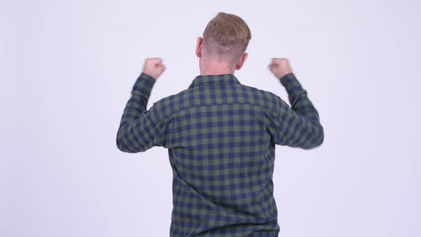 Cover Image for Rear View of Blonde Hipster Man Excited with Arms Raised