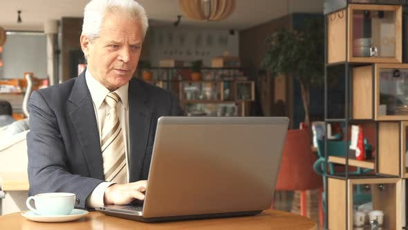 Thumbnail for Senior Businessman Uses Laptop at the Cafe