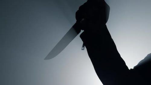Silhouette kriminelle Hand angreift mit Messer in Dunkelheit