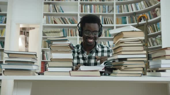 Thumbnail for Happy African Male Student Listening Music while Sitting at the Table in the Library