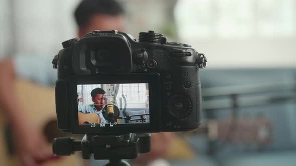Camera Display With Asian Boy Playing Guitar And Sing A Song While Streaming