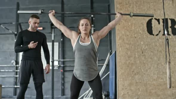 Cover Image for Personal Coach Watching Woman Squatting with Barbell