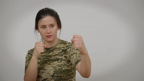 Serious Female Soldier Boxing Shadow with Confident Facial Expression