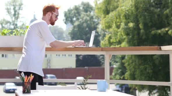 Thumbnail for Young Man Typing on Laptop, Standing in Balcony Outdoor