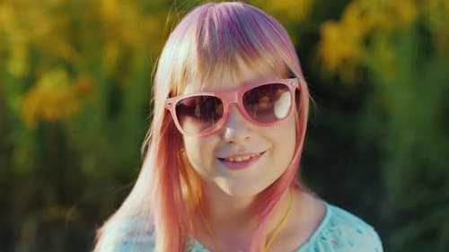 Portrait of a Cheerful Child in Pink Sunglasses with Pink Hair