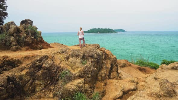 Thumbnail for tourist girl is standing on the stone coast of the sea and looking