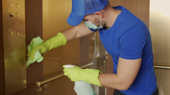 Man Wearing Gloves and a Mask Wipes the Buttons and Handrail of the Elevator
