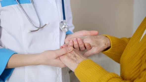 Doctor Holding Hands Of Elderly Woman Patient.