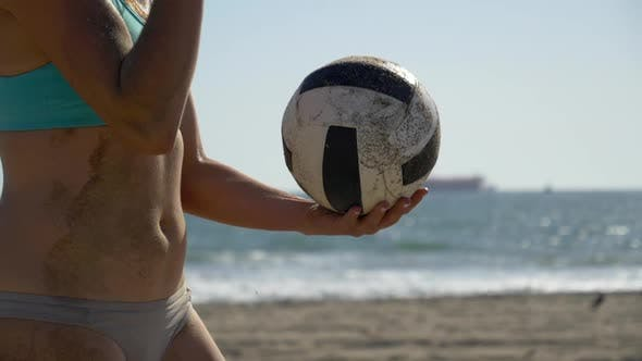 Thumbnail for Women players play beach volleyball and a player serves the ball.