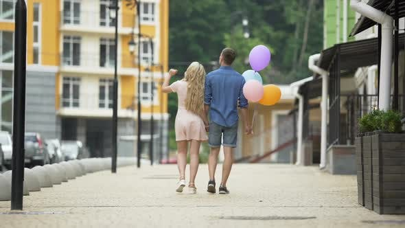 Thumbnail for Young couple walking down street holding hands, guy holding balloons, romantic
