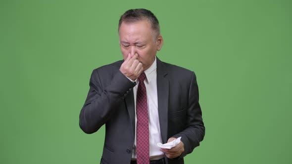 Mature Japanese Businessman Feeling Sick