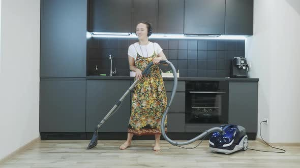 Thumbnail for Young happy woman in headphones vacuuming floor at home in kitchen using modern vacuum cleaner