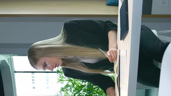 Elegant Woman Working in Stylish Office. Modern Blond Woman in Trendy Suit Sitting at Table in Light