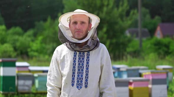 Beekeeper in protective workwear. Portrait of happy male beekeeper at apiary