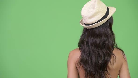 Rückansicht einer jungen multiethnischen Frau mit Hut, während sie die Aussicht im Urlaub genießt