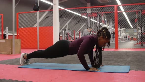 Sports Training  Africanamerican Woman Doing Push Ups in the Gym