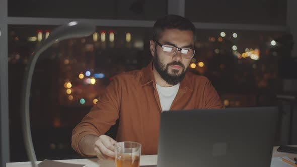 Thumbnail for Businessman Working on Laptop and Drinking Tea in Dark Office