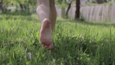 Baby Feet Running In The Grass