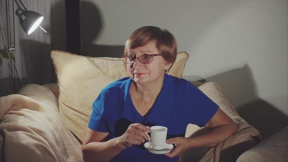 Older Woman Drinking Tea Sitting on the Chair