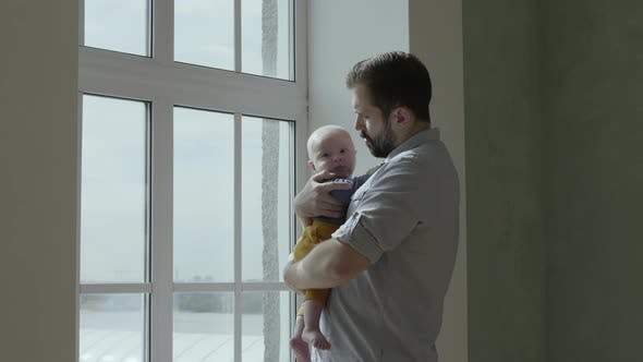 Thumbnail for Dad holding baby near a window