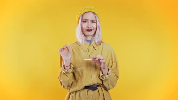 Thumbnail for Pretty Unusual Girl Breaking the Last Cigarette Isolated on Yellow
