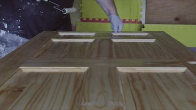 Worker Hand is Holding a Hand Roller Painting New Wooden Door with Paintbrush