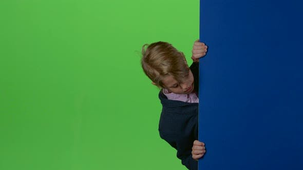 Thumbnail for Teenager Peeks Out From Behind the Boards and Shows Like on a Green Screen