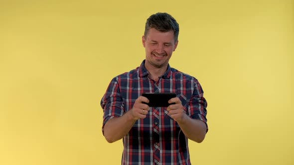 Thumbnail for Positive Young Man Enjoy Playing Online Game on Smartphone on Yellow Background