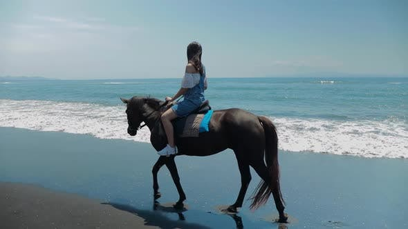 Thumbnail for Cute Chinese Teenager Rides a Horse On The Beach In Bali
