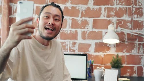 Asia businessman using phone talk to colleagues about plan in video call meeting while work.