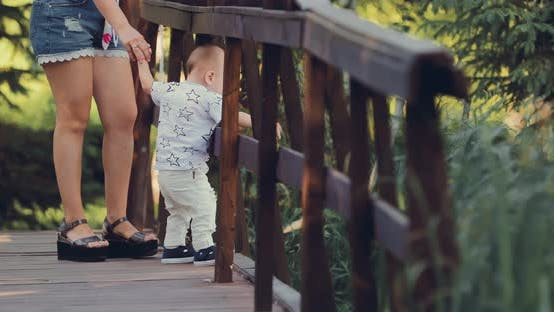 Kid Stands on a Wooden Bridge with His Mother and Looks Down