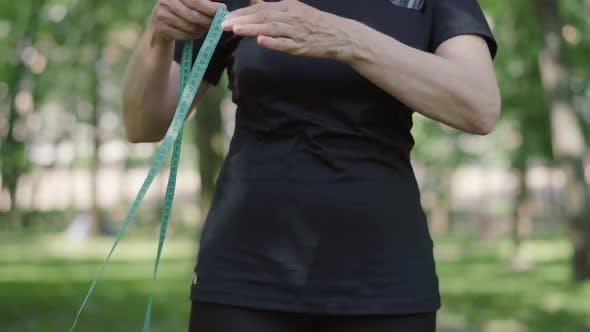 Thumbnail for Unrecognizable Mid-adult Sportswoman Measuring Waist with Tape, Confident Slim Caucasian Woman