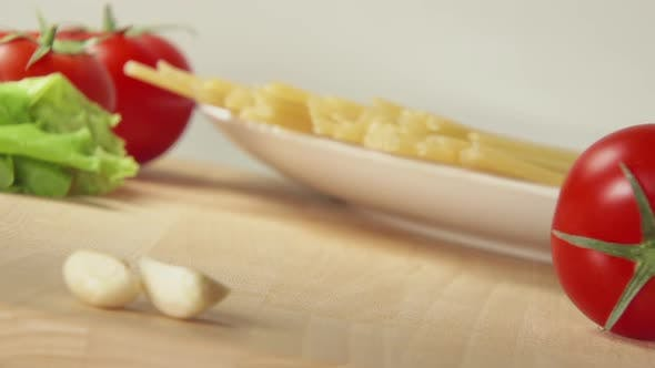 Thumbnail for Ripe Tomato Rolls On A Table Near Spaghetti And Garlic