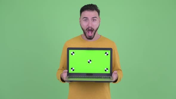 Thumbnail for Happy Young Handsome Bearded Man Showing Laptop and Looking Surprised