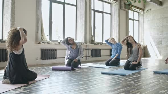 Cover Image for Women Warming Up in Yoga Class