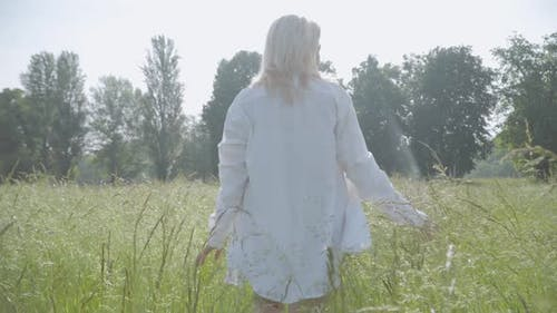 Back View of Blond Caucasian Overweight Woman Walking in Sunrays on Green Summer Meadow. Middle Shot