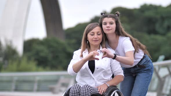 Thumbnail for Disabled Mother and Girl Making Heart with Hands