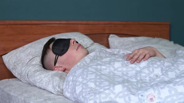Thumbnail for A Young Man Sleeps in a Sleep Mask. A Man Lies in Bed in His Room.