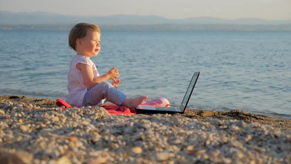 Cover Image for Baby Girl Sitting with Notebook on Seashore. New Generation of People Who Combine Work and Vacation