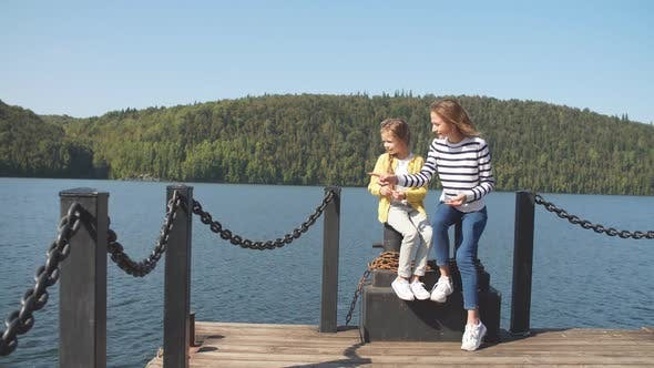 Mother and Daughter Sitting on Pier Warm Autumn Day
